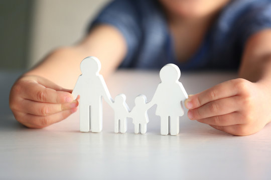Child holding figure in shape of happy family, closeup. Adoption concept