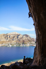 Young man climbing on overhanging cliff, his partner belaying. Telondos Island, Greece.