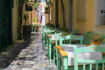 Tables and chairs of cafe are on the narrow street of Rethymnon (part of Old Town)