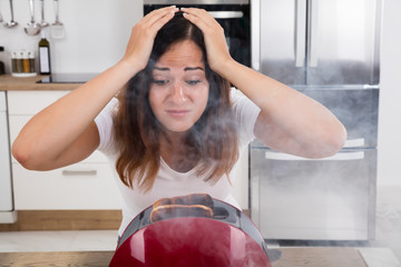 Frustrated Woman Looking At Burnt Toast In Toaster