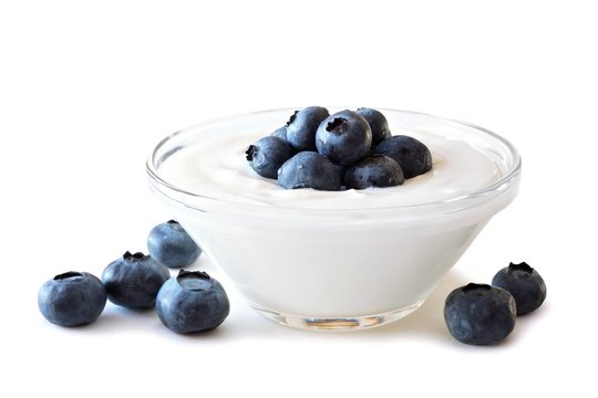 Clear bowl of yogurt with blueberries over a white background
