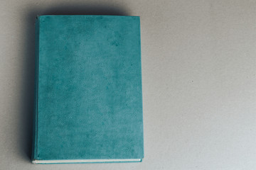 Blank old book on grey to replace your design. Top view.
