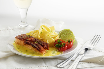 Salmon steak with lime sauce and tagliatelle, dish on a white table, copy space