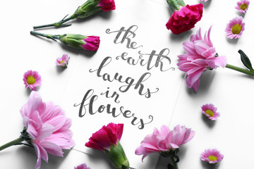 "Inscription ""THE EARTH LAUGHS IN FLOWERS"" written on paper with flowers on white background"