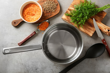 Stainless saucepan, parsley and lentil on grey kitchen table