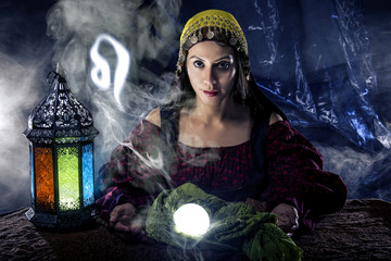 Psychic or fortune teller with crystal ball and horoscope zodiac sign of Leo