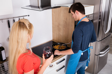 Woman Looking At Her Husband Preparing Dinner In Kitchen