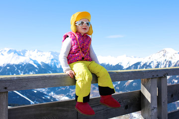 Happy child enjoying winter holidays in Alpine resort in Austria. Little girl playing in the snow. Kids having fun outdoors. Beautiful Alps mountains in the background.