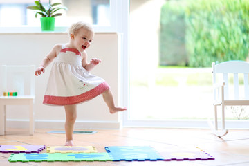 Funny toddler girl dancing indoors. Little child having fun moving and jumping in a sunny white room at home or kindergarten