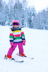 Happy child enjoying vacation in Alpine resort in Austria. Little girl skiing in mountains. Active sportive toddler learning to ski. Winter sport for family. Skier racing in snow.