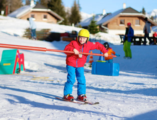 Happy school boy in colourful snowsuit learning to ski in alpine resort on sunny day during winter vacation