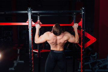 Strong man doing pull ups handsome athlete at gym. big confident muscular  training.
