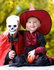 Portrait of little girl in Halloween witch costume and her teenage devil brother holding pumpkin and skull decoration