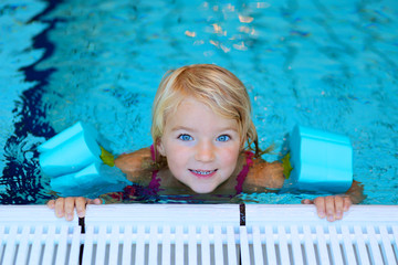 Happy preschooler girl learning to swim in community swimming pool. Little swimmer enjoying group lesson at sport school.