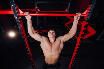 0e6b29a998 Strong man doing pull ups handsome athlete at gym. big confident muscular  training.