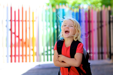 Happy little girl going to school. Cute preschooler kid with backpack enjoying first school day. Little student standing in front of the colorful pencil shape fence. Educational concept.