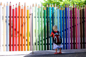 Happy little girl going to school. Cute preschooler kid with backpack enjoying first school day. Little student standing in front of the colorful pencil shape fence looking at the schoolyard.