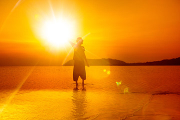 Silhouette of man holding sun at bright golden tropical sunset