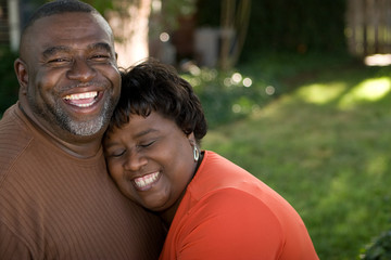 Mature African American couple laughing and hugging.