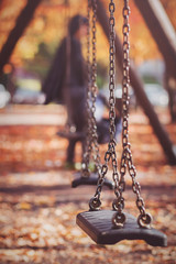 Swings with chains in a park in autumn, with fallen leaves and some children blurred in background