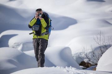 Fotografo con macchina e teleobiettivo nella neve