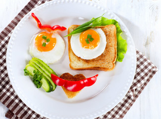 Fried eggs with toast and fresh vegetables for a breakfast.