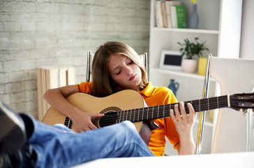 boy enjoys playing the guitar