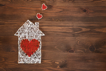 Home sweet home. Handmade home symbol with heart shape on wooden