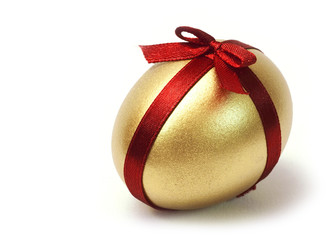 Easter Gold egg with red ribbon cross and bow on white background isolated.