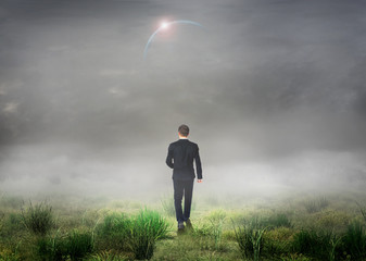 The concept of the unknown. Man in suit walk in fog on grass fie
