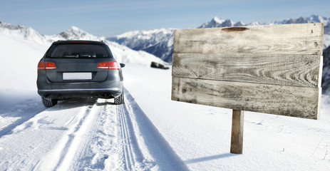 winter road and car with road sign