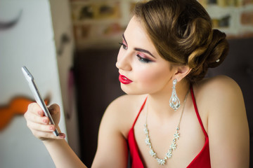 Girl in evening dress looking in the phone. Close-up