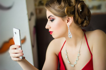 Girl in evening dress and makeup makes selfie. Close-up