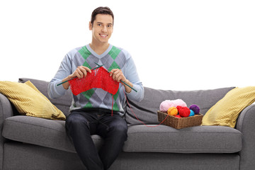 Happy man sitting on a sofa and knitting