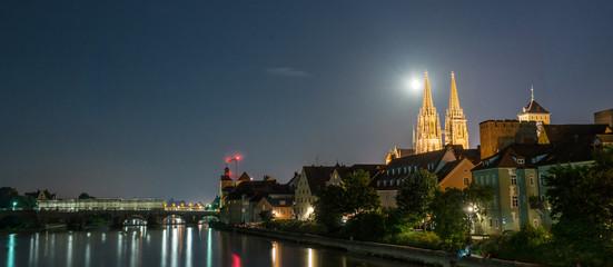 Nachtaufnahme von Regensburg mit Mond neben dem Dom