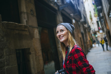 Spain, Barcelona, portait of smiling young woman with camera at Gothic Quarter