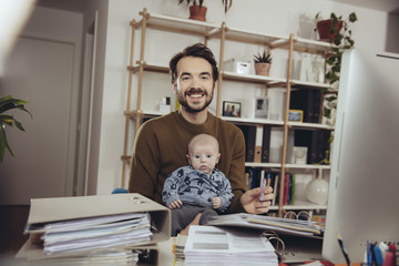 Portrait of smiling father with his baby in home office