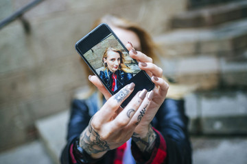 Tattooed woman's hands taking  selfie with smartphone, close-up
