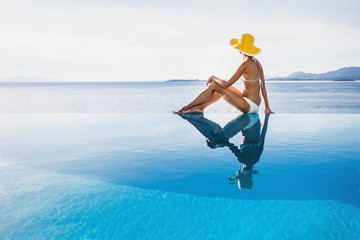 Young woman enjoying a sun in the infinity pool. Vacations and summer concept