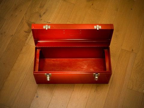 Empty red tool box on wooden floor