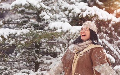 Winter fun. Beautiful  woman playing with snow in forest
