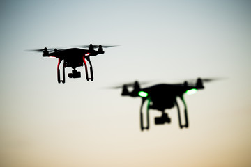 Two drones silhouette flying under the clear sky background