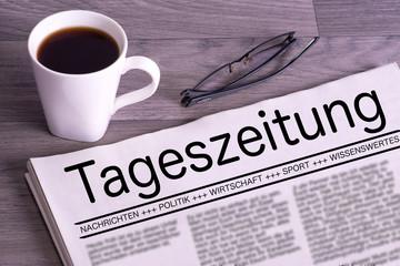 Eine Zeitung, Lesebrille und eine Tasse Kaffee