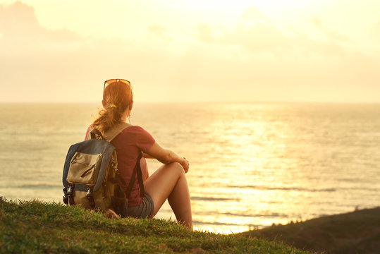 Young girl with backpack enjoying sunset listening to music on p
