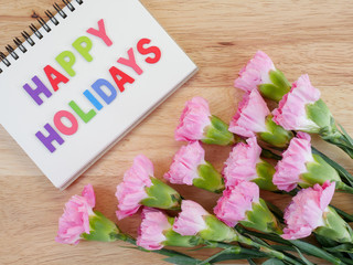Wooden word spell Happy Holidays and sweet pink carnation flower