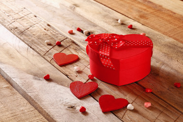 Red hearts and present box on wooden table