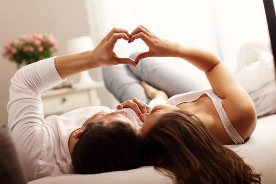 Happy couple making heart shape in bedroom