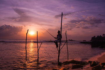 Silhouettes of the traditional Sri Lankan stilt fishermen at the sunset in Weligama, Sri Lanka. Stilt fishing is a method of fishing unique to the island country of Sri Lanka