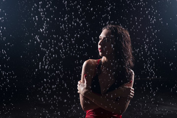 Sensual woman under water drops. Dark background