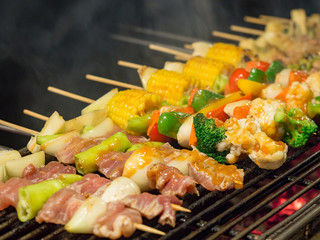 Barbecue grill with assorted delicious meat and vegetable over the coals.